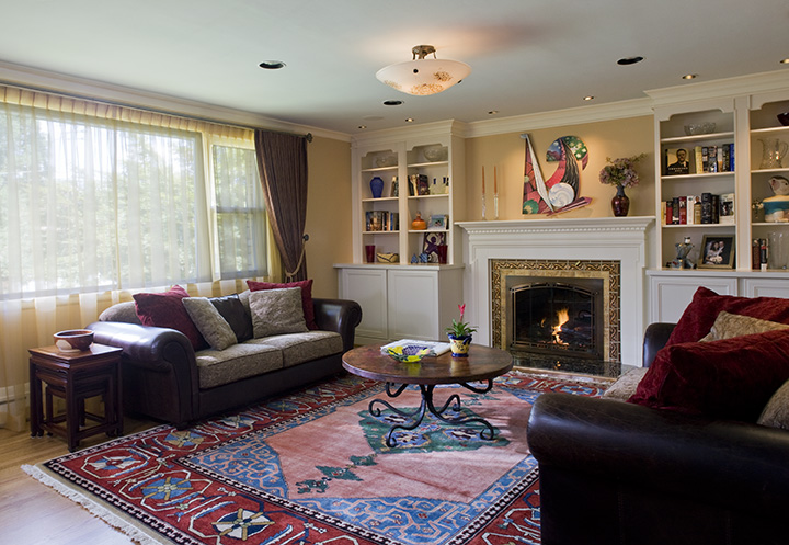 LIVING ROOM WITH NEW FIREPLACE TREATMENT, CABINETS. ANTIQUE CARPET SETS OFF FATHER'S CONTEMPORARY PAINTINGS.