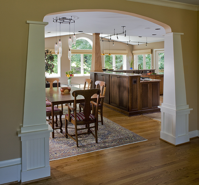 WIDENED OPENING TO DINING AREA REPEATS COLUMN AND ARCH DETAIL FROM ENTRY.