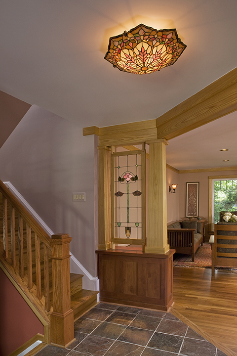 RECLAIMED, RESTORED ANTIQUE STAINED GLASS PANEL DEFINES FOYER, NEW RAILING OPENS SPACE TO VIEW.
