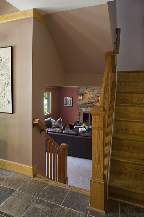 LOWER LEVEL BECOMES PART OF LIVING SPACE BY REMOVING WALL BETWEEN STAIR FLIGHTS.