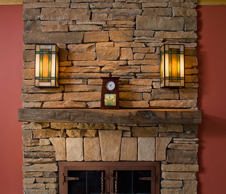 FIREPLACE WITH STONE CLADDING, RECLAIMED MANTEL AND STAINED GLASS SCONCE LIGHTS.