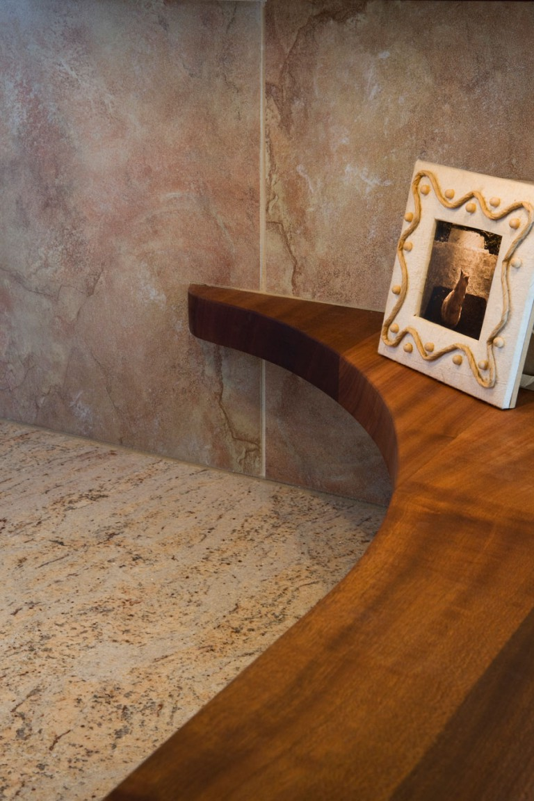 NARROW SAPELE MAHOGANY COUNTERTOP FINISHES WITH A CURVE TO THE WALL CREATING A PLACE FOR DISPLAY.